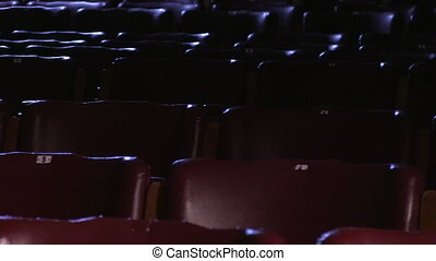 Empty cinema chairs - A sliding shot of empty cinema chairs.