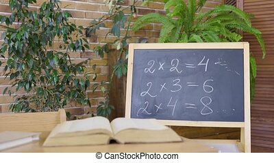 Empty classroom with chalkboard, desk and textbook. School, home education, distance learning. Studying arithmetic in primary grades, first lesson, school knowledge. Interior of modern empty classroom.
