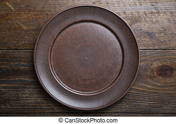 empty clay plate on wooden background