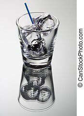 Empty cocktail tumbler with ice cubes