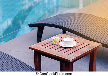 Empty Coffee Cup With Sweet Candy On Wooden Table Neear Swimming Pool In  Summer.