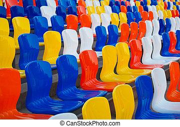 Empty colourful plastic seats at football stadium