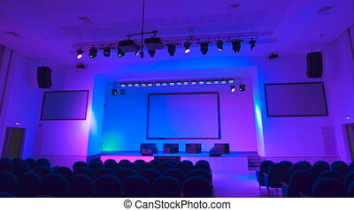 Empty concert hall which employs a large number of professional stage lighting equipment. Multi-colored lights illuminate the modern hall.