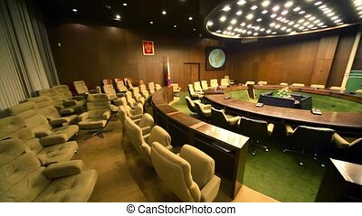 Empty conference room with ring tables and rows of chairs