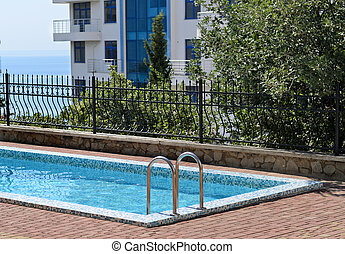 Empty cool blue swimming pool at an apartment block or vacation accomodation at the coast