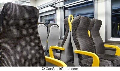 Empty corridor and seats in modern train wagon. Black and...