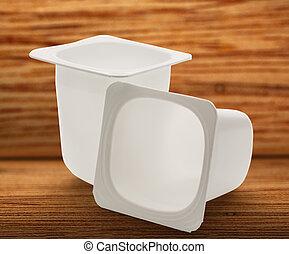 Empty crushed plastic yogurt pots on wooden background