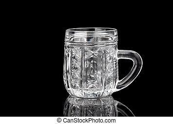 Empty crystal mug on a black background with reflection.