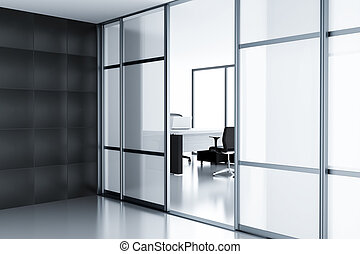 Empty cubicle with laptop on table behind a glass doors in...