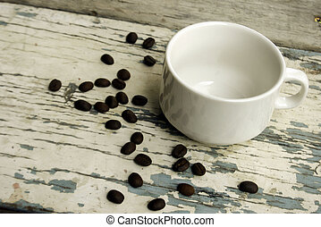 Empty cup of coffee with coffee beans on the table