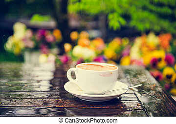 Empty cup of coffee with traces of lipstick on the table under the rain, outdoors, toned image