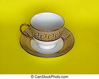 Empty cup on a saucer with a pattern on a yellow background