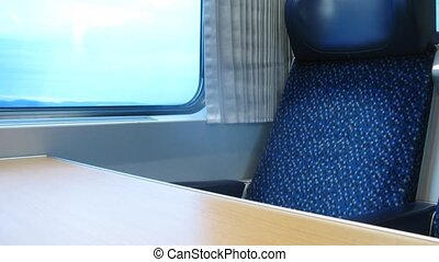Empty dark blue armchair stands near window of moving train