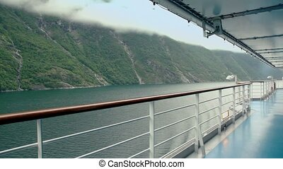 Empty deck of ship float on fiord near mountain with forest