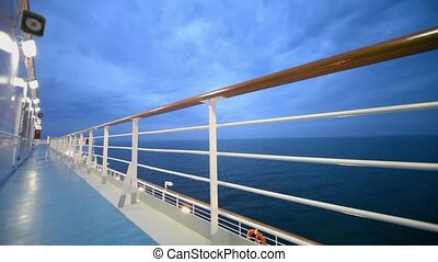Empty deck of ship which float on sea at evening during...