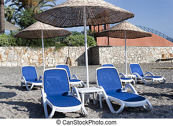 Empty deckchairs and umbrellas with a thatched roof on the beach in Turkey