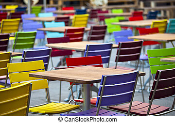 Empty dining tables and coloured chairs in a street cafe