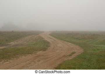 Empty Dirt Road in Countryside on Foggy Morning