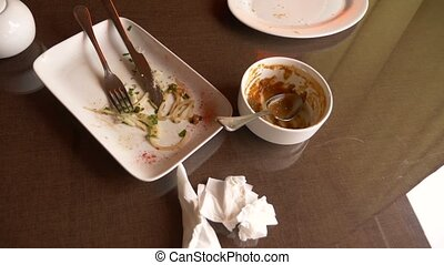 Empty dirty white plates with fork, spoon and waste food...