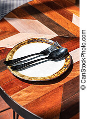 empty dish with spoon and fork on table