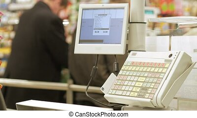 Empty electronic cash desk at the grocery store. Against the background people make purchases
