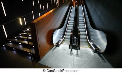 Empty escalator moves in empty hall. - Empty escalator moves...