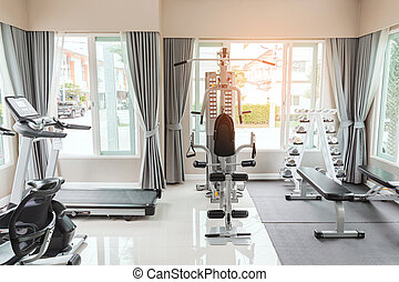 Empty gym or exercise room has many types of equipment but no one uses them.