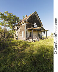 Abandoned farm house in rural field.