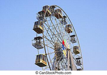 Empty ferris wheel on blue sky background