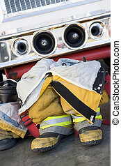 Empty firefighter\'s boots and uniform next to fire engine