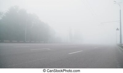 Empty foggy road markings and one car