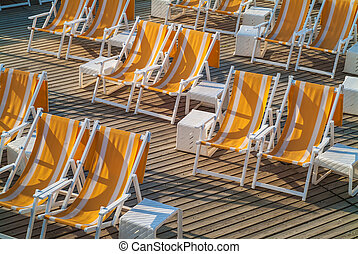 Empty folding beach chairs on a wooden deck