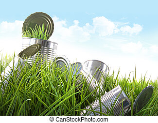 Empty food cans in grass with blue sky