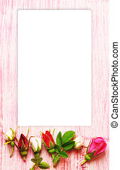 empty frame greeting label rose buds on a pink wooden background in retro style shabby chic top view