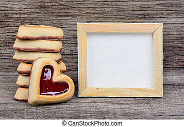 Empty frame with heart cookies on table