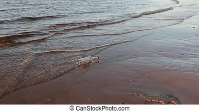 empty glass bottle washes the waves of the sea in the evening