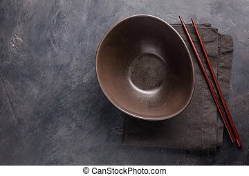 Empty glass bowl of Chinese noodles and wooden sticks on...
