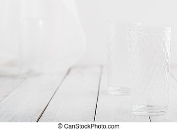 Empty glass on white wooden table. Space for text.