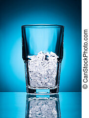 Empty glass with ice isolated on a blue background