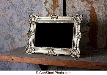 Empty gold frame on a shelf
