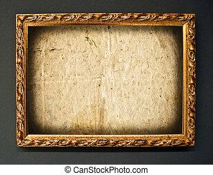 Empty golden frame on grunge wall