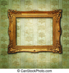 Empty golden frame on Victorian floral green-gold wallpaper