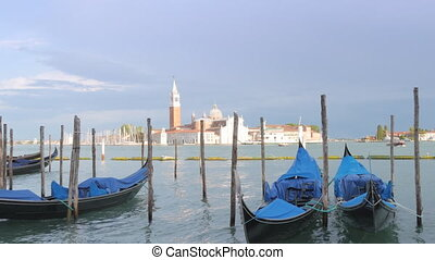 Empty gondola in Venice on waves waiting for tourists in...