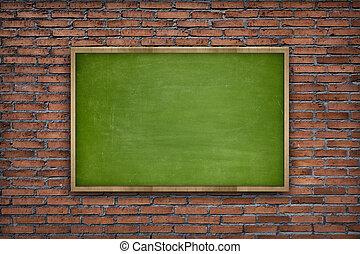 Empty green blackboard on brick wall