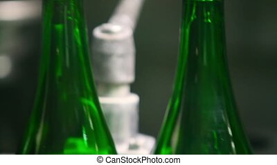 Empty green bottles for champagne are moving along the...