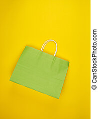 empty green paper shopping bag with a handle on a yellow background