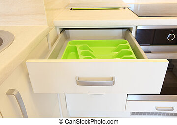 Empty green plastic cutlery tray in kitchen drawer