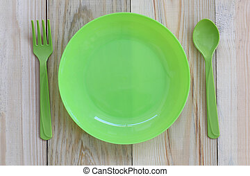 Empty green plastic dish and spoon placed on wooden floor.