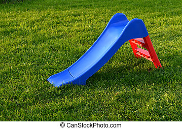 Empty green slide on grass in park