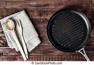 Empty grill pan with wooden spatula and spoon